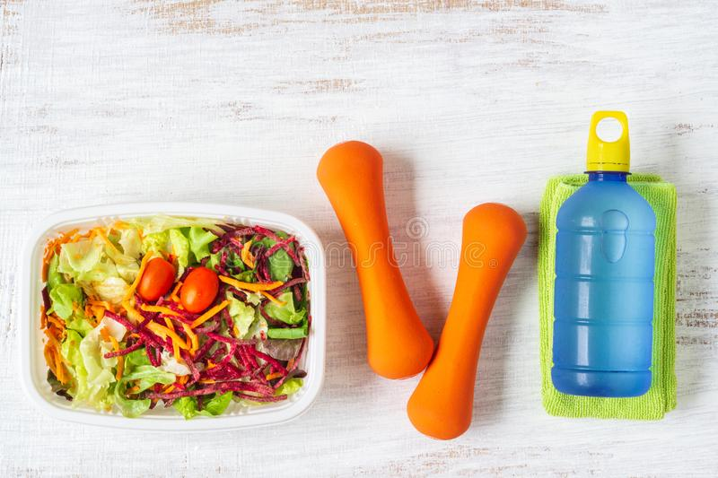 Fresh vegetable salad in lunch box with orange dumbbells excercise equipment and energy water drink on white rusty wood background. Active healthy lifestyles royalty free stock photography