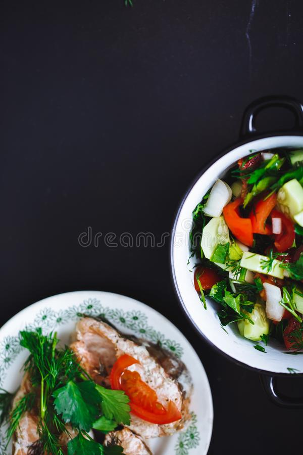 Fresh vegetable salad in plate and fish on black background, close up, top view. Healthy food. royalty free stock images