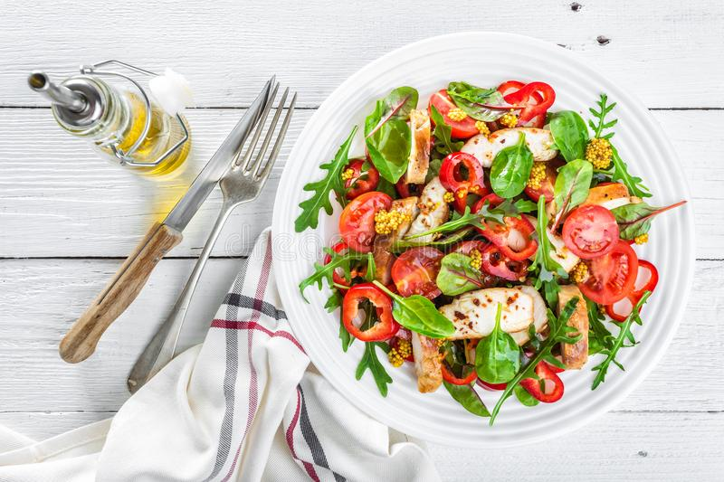 Fresh vegetable salad plate of tomatoes, spinach, pepper, arugula, chard leaves and grilled chicken breast. Fried chicken meat, fi. Llet with salad. Healthy food stock photo