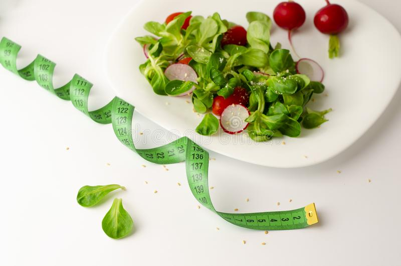 Fresh vegetable salad of radish, tomatoes and corn salad or Valerianella locusta. Close up on white plate and measuring tape. Diet, weight loss and slimming royalty free stock image