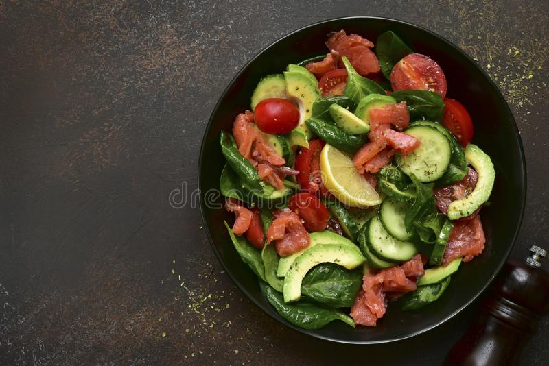 Fresh vegetable salad with salted salmon.Top view with copy space. Fresh vegetable salad with salted salmon in a black plate over dark slate, stone or concrete royalty free stock photo