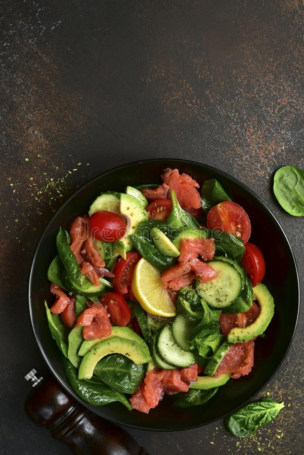 Fresh vegetable salad with salted salmon.Top view with copy space. Fresh vegetable salad with salted salmon in a black plate over dark slate, stone or concrete royalty free stock image