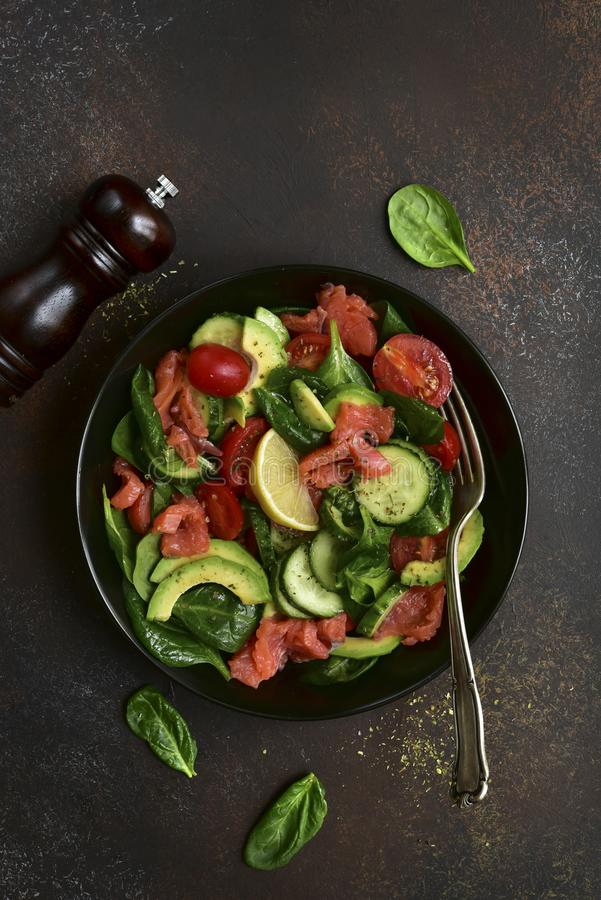 Fresh vegetable salad with salted salmon.Top view with copy space. Fresh vegetable salad with salted salmon in a black plate over dark slate, stone or concrete stock photo