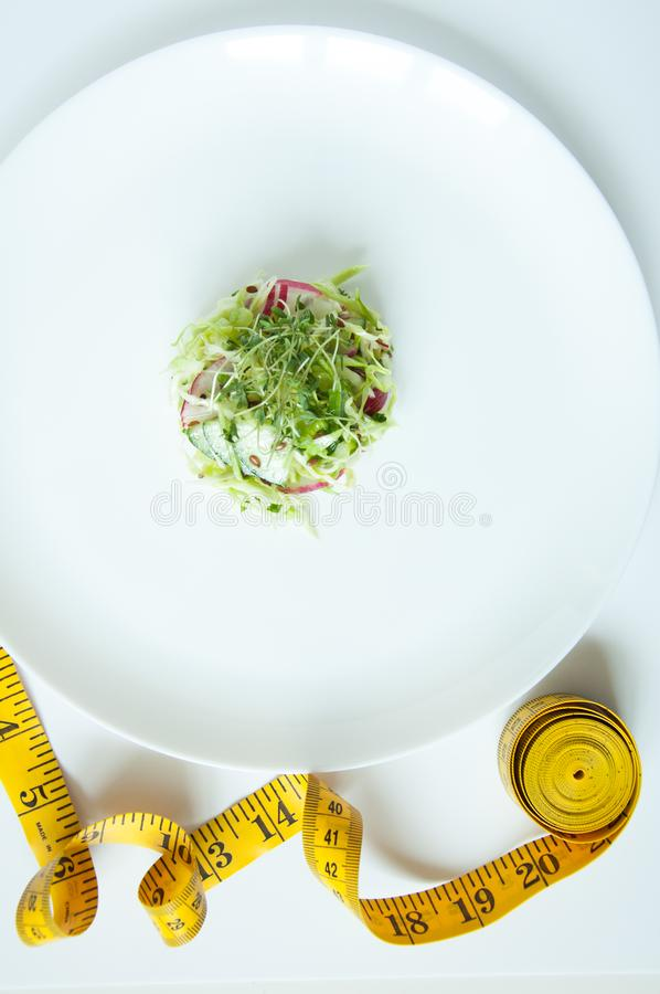 Fresh vegetable salad on a white plate. Dietary nutrition. Vegan food. Microgreen, flax seeds in food. To eat and lose weight. Yellow tape for measurement on royalty free stock photo