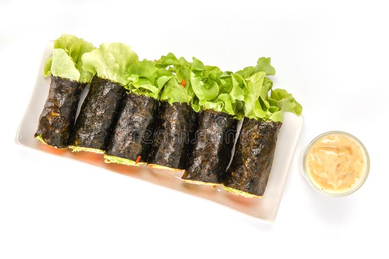 Fresh vegetable spring roll, salad roll in Seaweed tube on ceramic plate, clean food, salad for weight loss and vegetarian. On white background stock photos