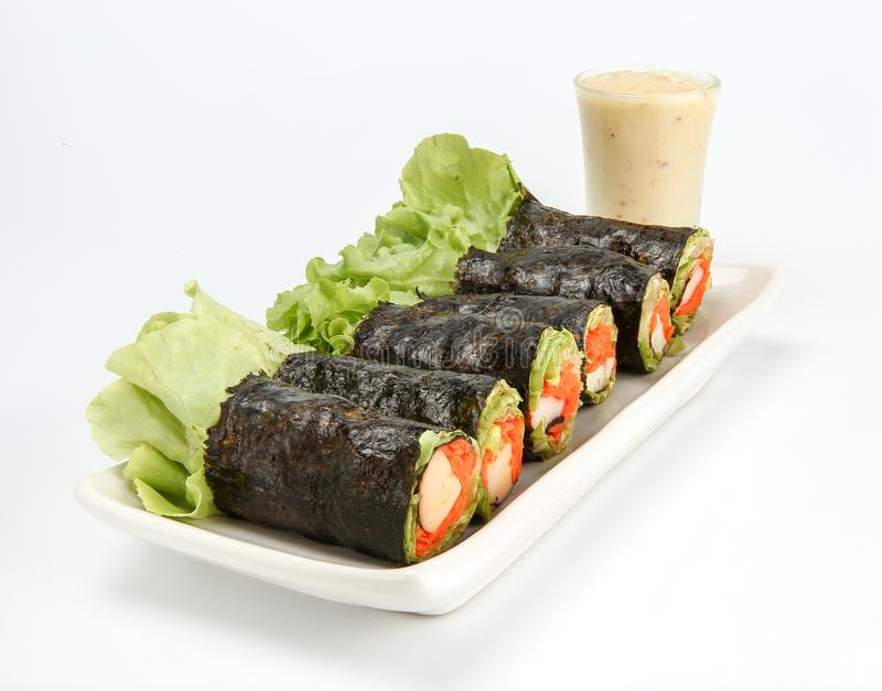 Fresh vegetable spring roll, salad roll in Seaweed tube on ceramic plate, clean food. Salad for weight loss and vegetarian, on white background stock photo