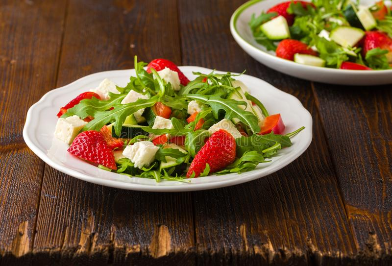 Fresh vegetable strawberry salad on white plate on natural rustic desk. royalty free stock photo