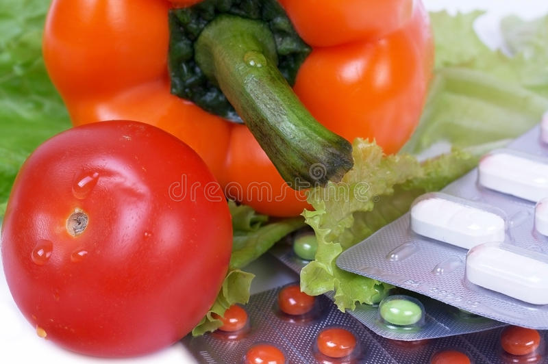 Fresh vegetables. Closed-up pepper and tomato on salat near pills royalty free stock image