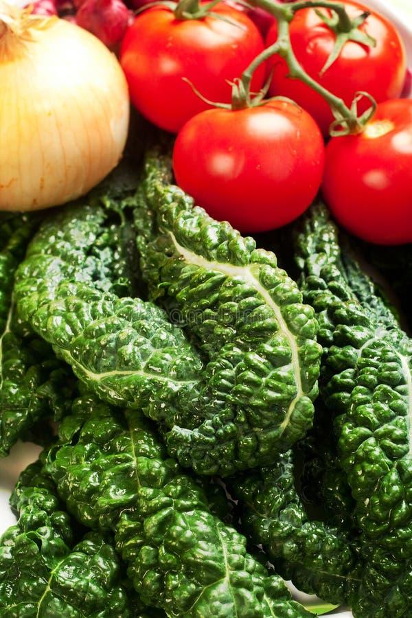Fresh Vegetables. Fresh tomatoes, tuscan black kale, yellow onion and pearl onion stock photo
