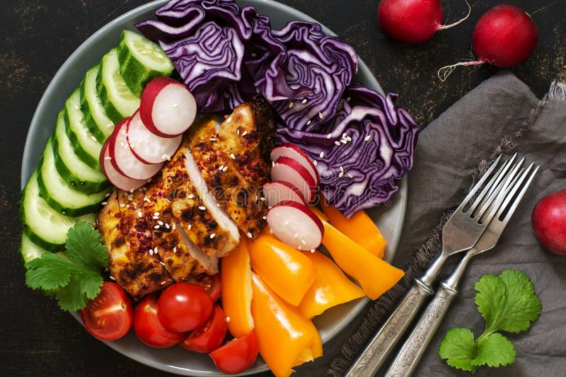 Fresh vegetables with baked chicken breast close up on rustic background,top view. Red cabbage, radish, sweet pepper, cilantro,cuc stock photo