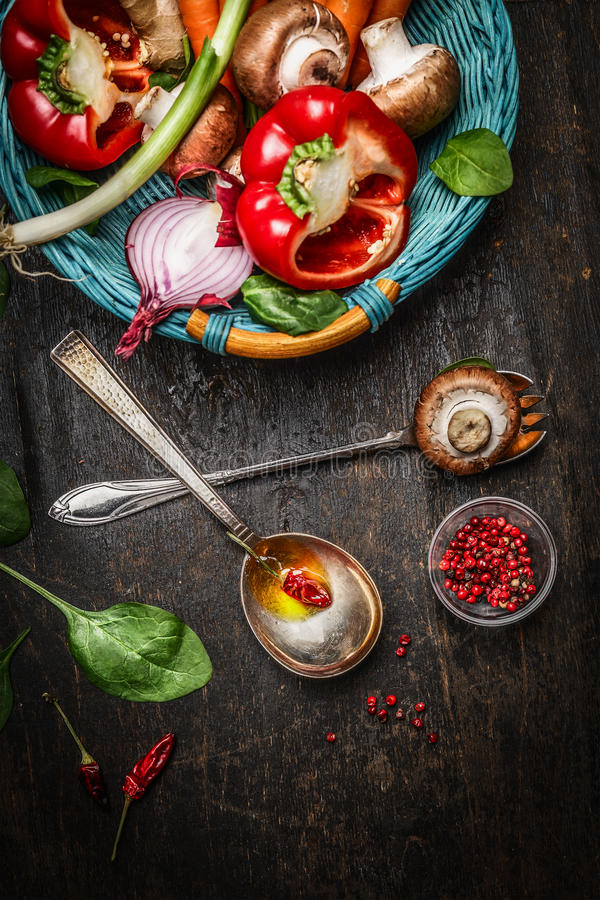Fresh vegetables in basket, cooking spoons with oil and spices on rustic wooden background, top view. royalty free stock images