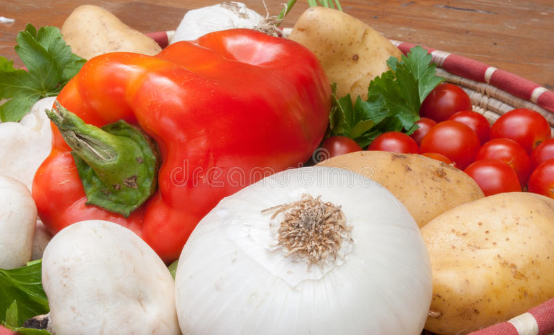 Fresh vegetables. A basket with mushrooms, peppers, white onion and tomatoes stock photography