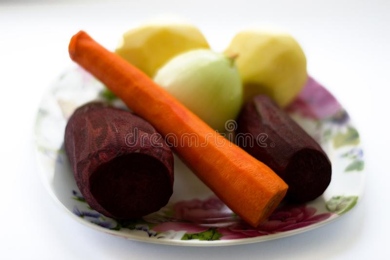 Fresh vegetables - beet, carrot, potato, onion on plate isolated on white background. Ingredients prepared for cooking soup. royalty free stock photo
