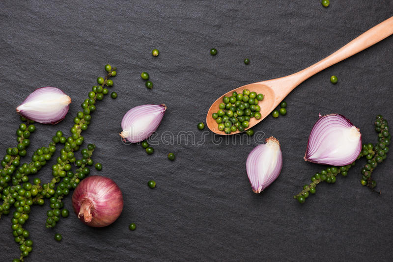Fresh vegetables on black table. Red onion rings and green peppercorns. Top view. royalty free stock photo