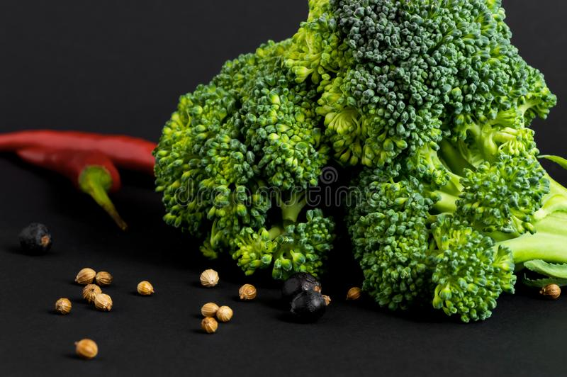 Fresh vegetables - broccoli and chili, different spices, on black background. Healthy food stock image