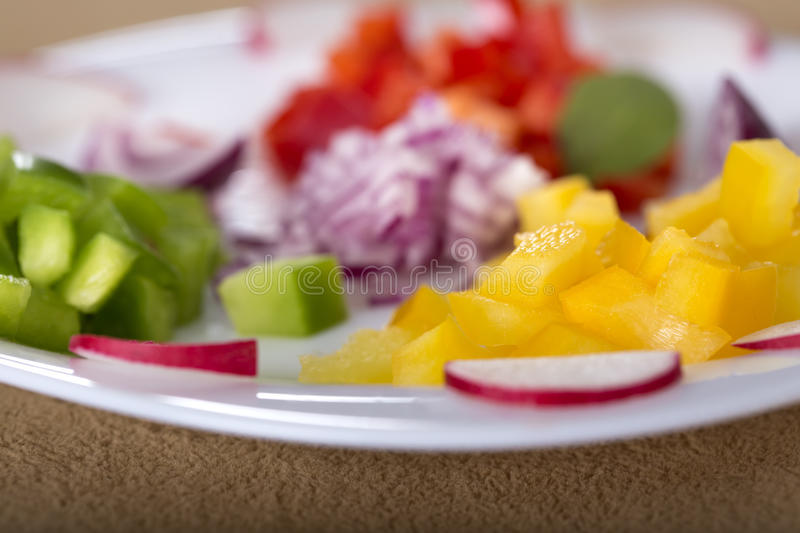 Fresh vegetables. Close up of some fresh chopped vegetables on white plate for salad royalty free stock image