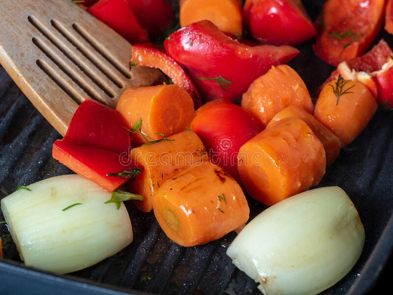 Fresh vegetables are cooked in a pan-grill, mixed with a wooden spatula. Carrot, sweet red pepper, onion. royalty free stock images