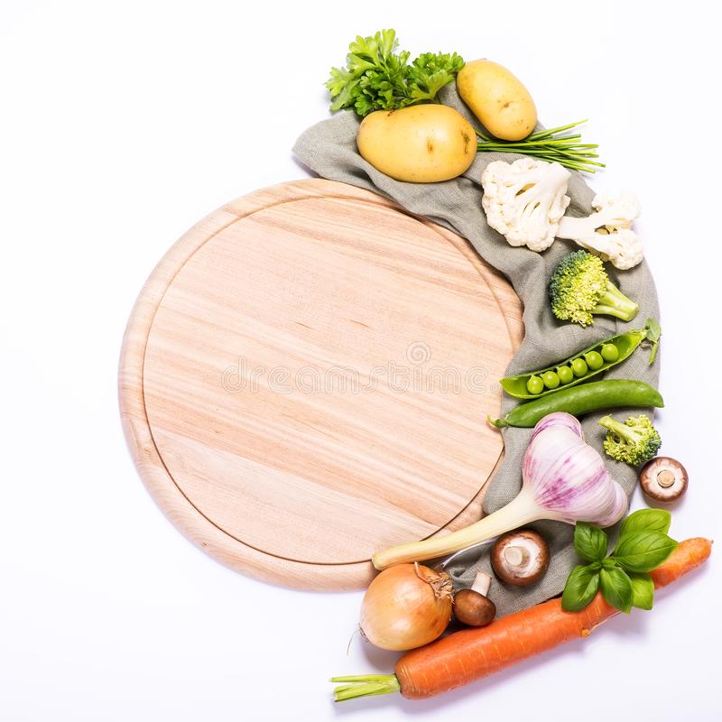 Fresh vegetables for cooking around round empty cutting board, ingredients for healthy eating, copy space white background. Place for text, vegan and royalty free stock images
