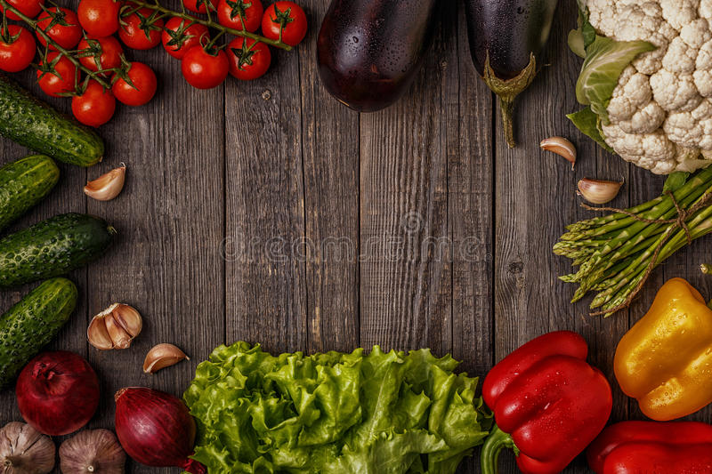 Fresh vegetables for cooking on dark wooden background. royalty free stock photo
