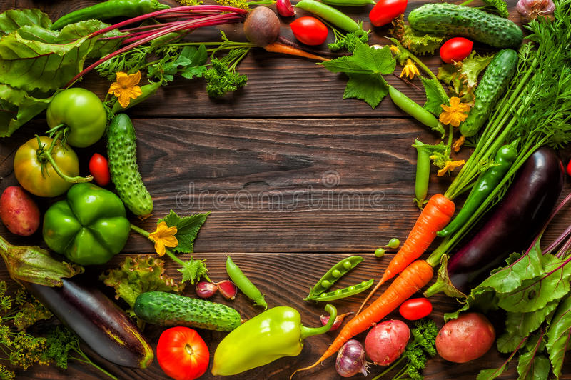 Fresh vegetables for cooking on dark wooden background with space for text. stock image