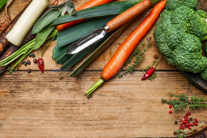 Fresh vegetables for cooking with peeler on wooden background, top view, border. royalty free stock photo