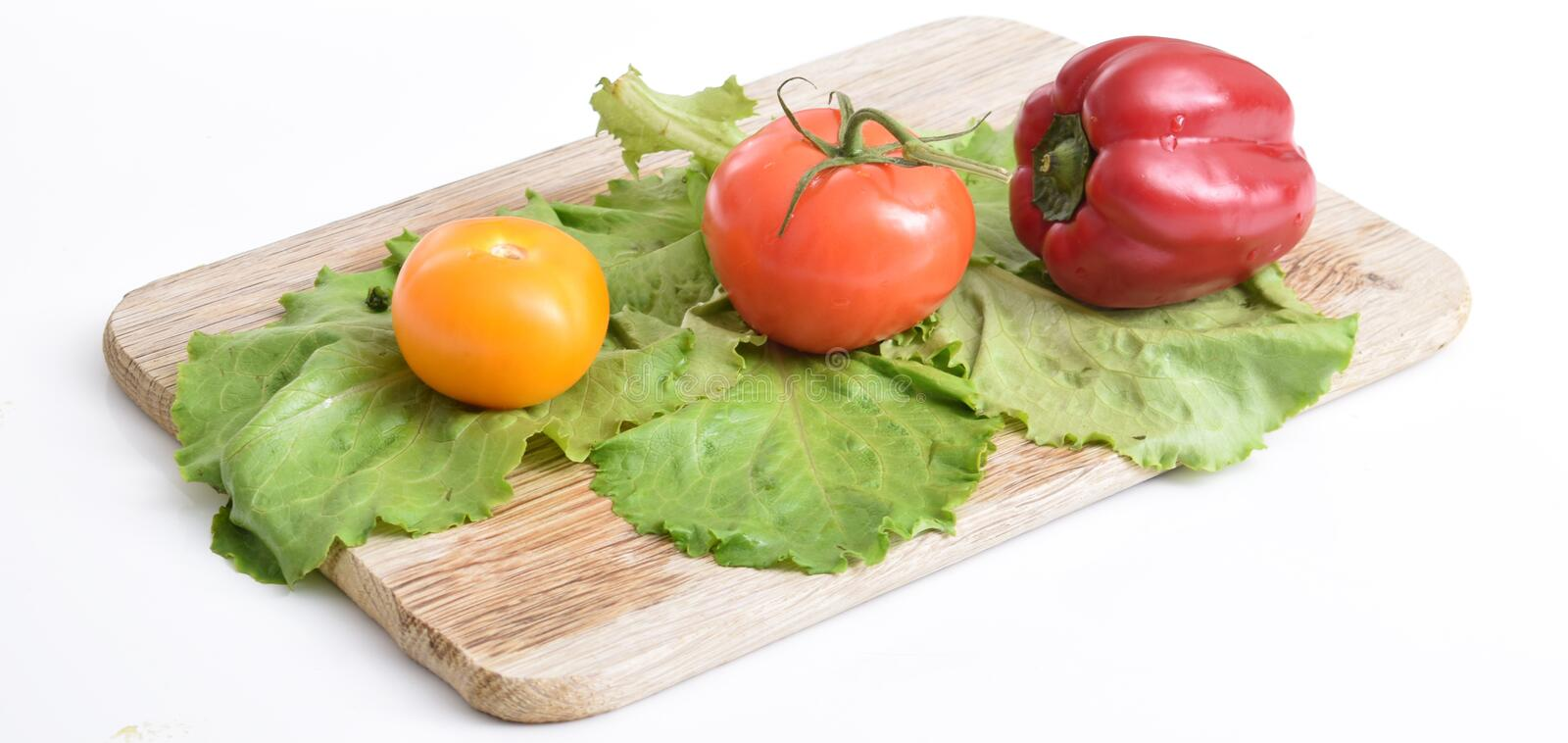 Fresh vegetables on a cutting board. Culinary composition of fresh natural vegetables on a white background: red, yellow tomatoes, bell peppers and green fresh stock image