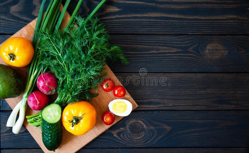 Fresh vegetables on a cutting board with herbs for salad on a dark background. Diet food top view with place for text.  stock photography