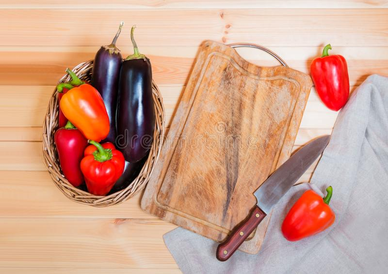 Fresh vegetables, cutting board and kitchen knife on wooden background. stock photo