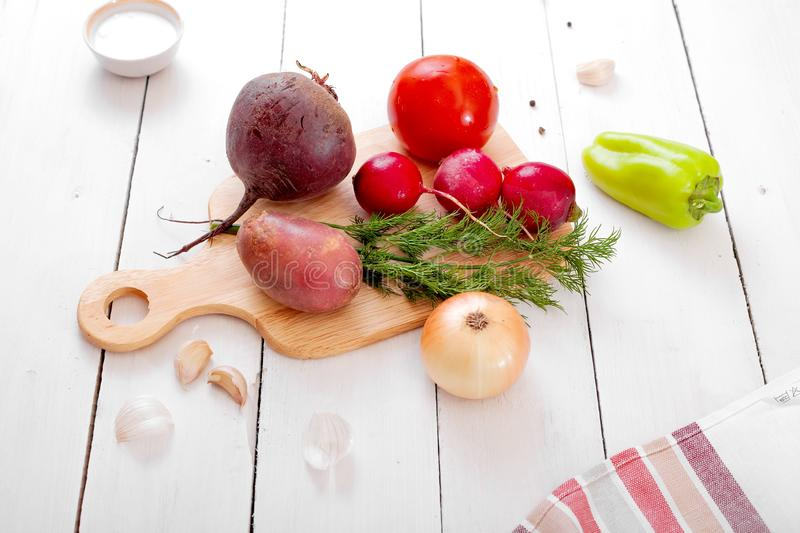 Fresh vegetables on a cutting board - radishes, beets, potatoes, dill, tomato, sweet peppers. Light wooden background - rustic style stock image
