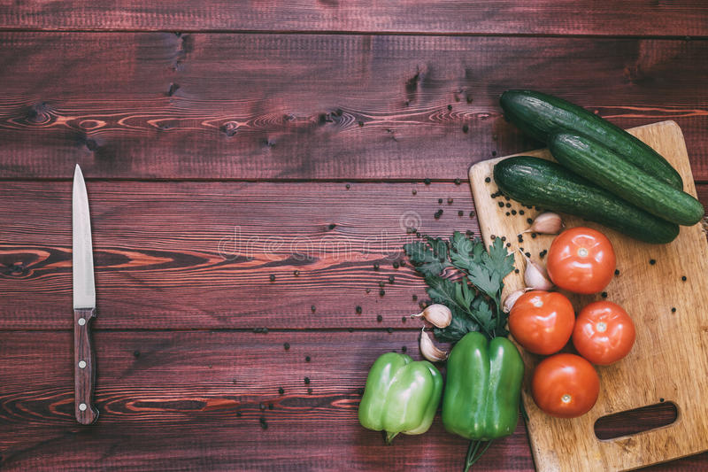 Fresh vegetables on cutting board. tomato, cucumber, bell pepper, garlic, spices. Wood background. kitchen workplace concept. top view. copy space royalty free stock images