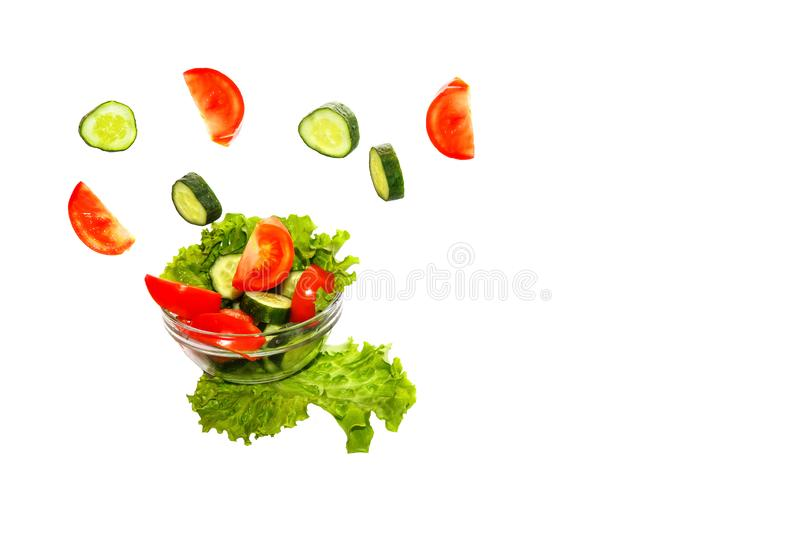 Fresh vegetables falling into a plate on a white background in slow motion stock photography