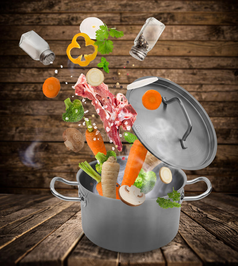 Fresh vegetables falling into stainless steel pot. stock images