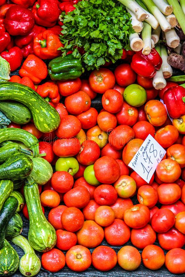 Fresh vegetables on the farmers market. Handwritten paper in Portuguese with names of the vegetable sort and price. Organic food. Red tomatoes, green zucchinis royalty free stock image