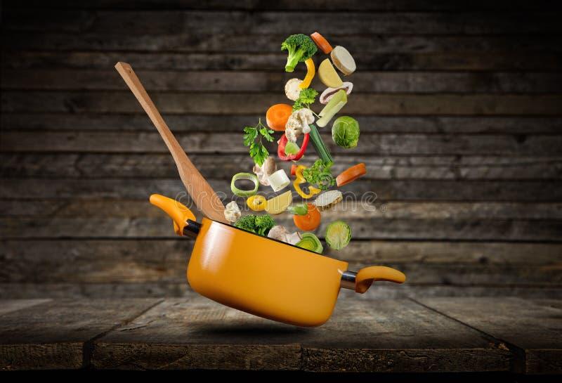 Fresh vegetables flying into a pot stock photos