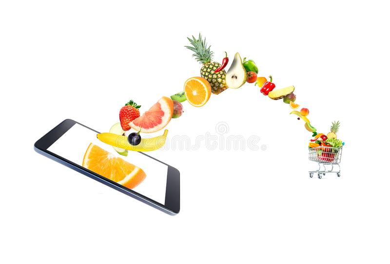 Fresh vegetables and fruits flying into a crowded shopping cart from a modern gadget, mobile phone, isolated on a white background stock image