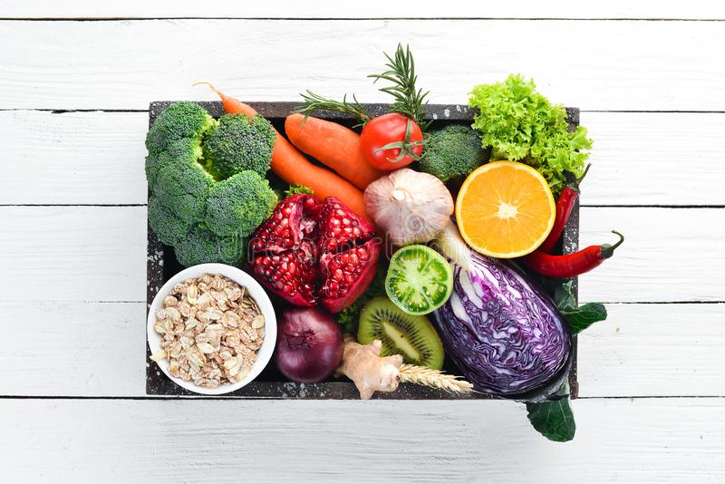 Fresh vegetables and fruits in a wooden box on a white wooden background. Organic food. Top view. Free copy space stock images