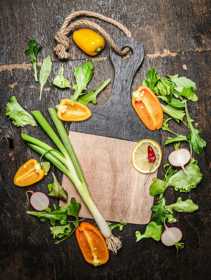 Fresh vegetables and herbs ingredients for tasty cooking around blank cutting board on rustic wooden background royalty free stock photography
