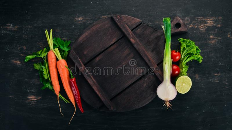 Fresh vegetables and ingredients for cooking around vintage cutting board on rustic background stock images