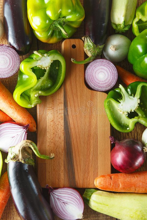 Fresh vegetables and ingredients for cooking around vintage cutting board on rustic background, top view, place for text. Vegan stock image