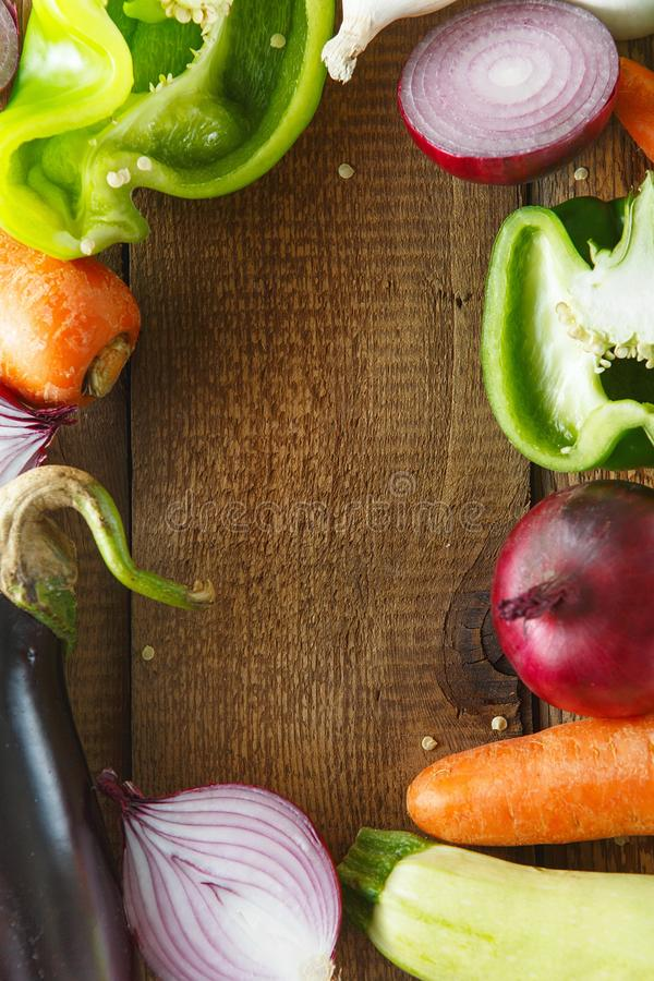 Fresh vegetables and ingredients for cooking around vintage cutting board on rustic background, top view, place for text. Vegan. Food, vegetarian and healthily stock images