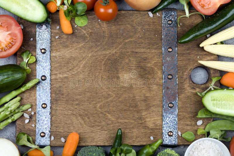 Fresh vegetables and ingredients for cooking around vintage cutting board on rustic background. Top view, place for text. Vegan food , vegetarian and healthily stock photo