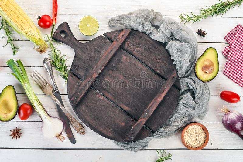 Fresh vegetables and ingredients for cooking around vintage cutting board on rustic background, top view, place for text. Vegan food , vegetarian and healthily royalty free stock photos