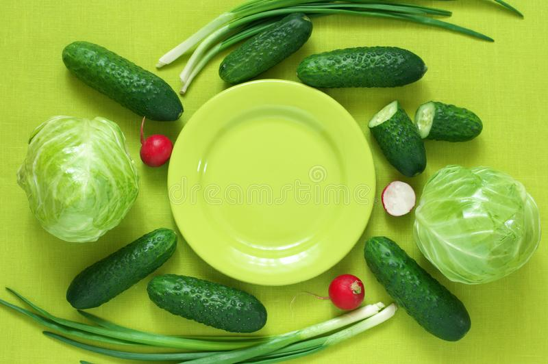 Fresh vegetables and plate on green royalty free stock photography