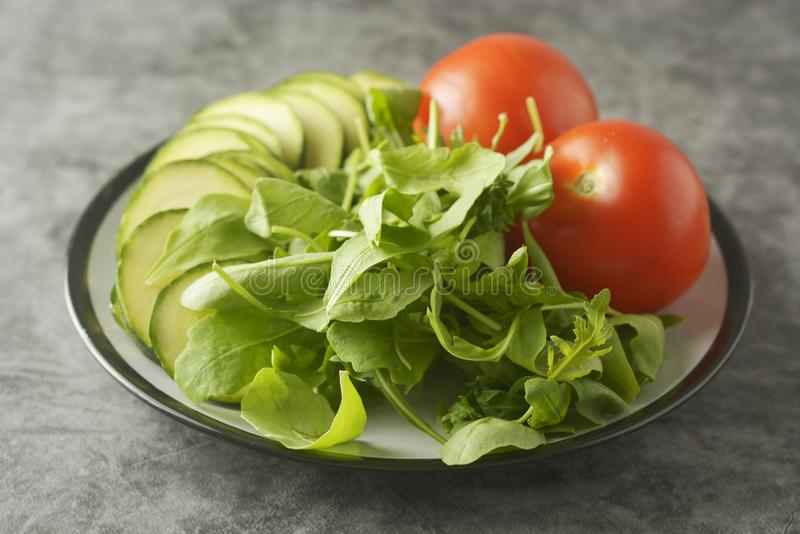 Fresh vegetables in a plate - salad mix, tomatoes and zuchinni. Healthy food concept, lose weight stock photos