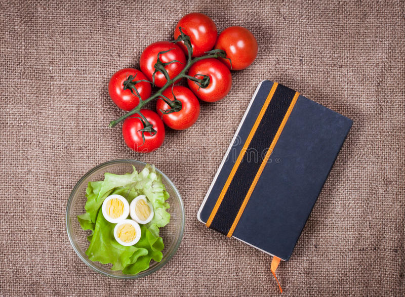 Fresh vegetables and recipe book on sackcloth royalty free stock photos