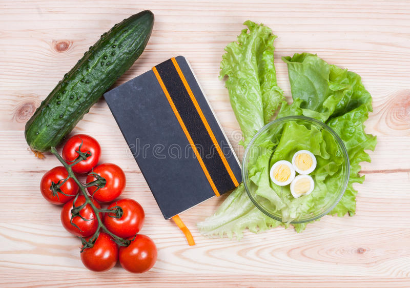 Fresh vegetables and recipe book on sackcloth stock photos