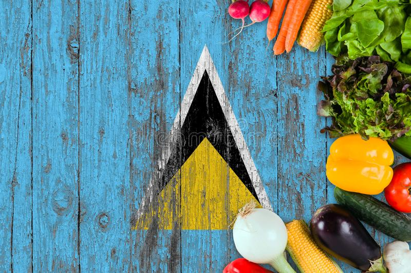 Fresh vegetables from Saint Lucia on table. Cooking concept on wooden flag background stock image
