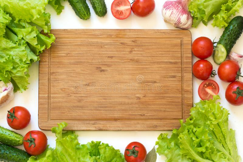 Fresh vegetables for salad. Raw green lettuce, greens, tomato. Top view. Copy space on wooden cutting board. Clean eating, vegan. stock image