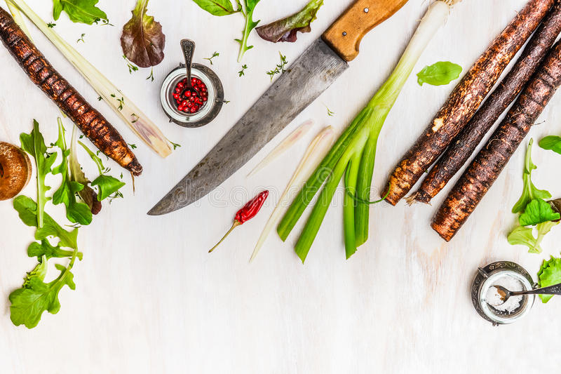 Fresh vegetables and seasoning ingredients for healthy cooking with kitchen knife on white wooden background. Top view, border royalty free stock photos