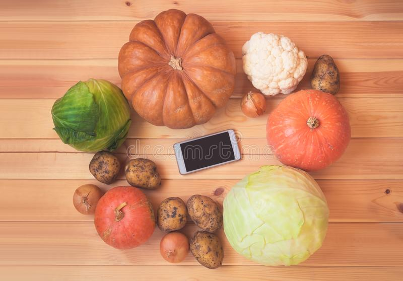 Fresh vegetables and smartphone on wooden background. Concept of digital recipe book and shopping list royalty free stock images